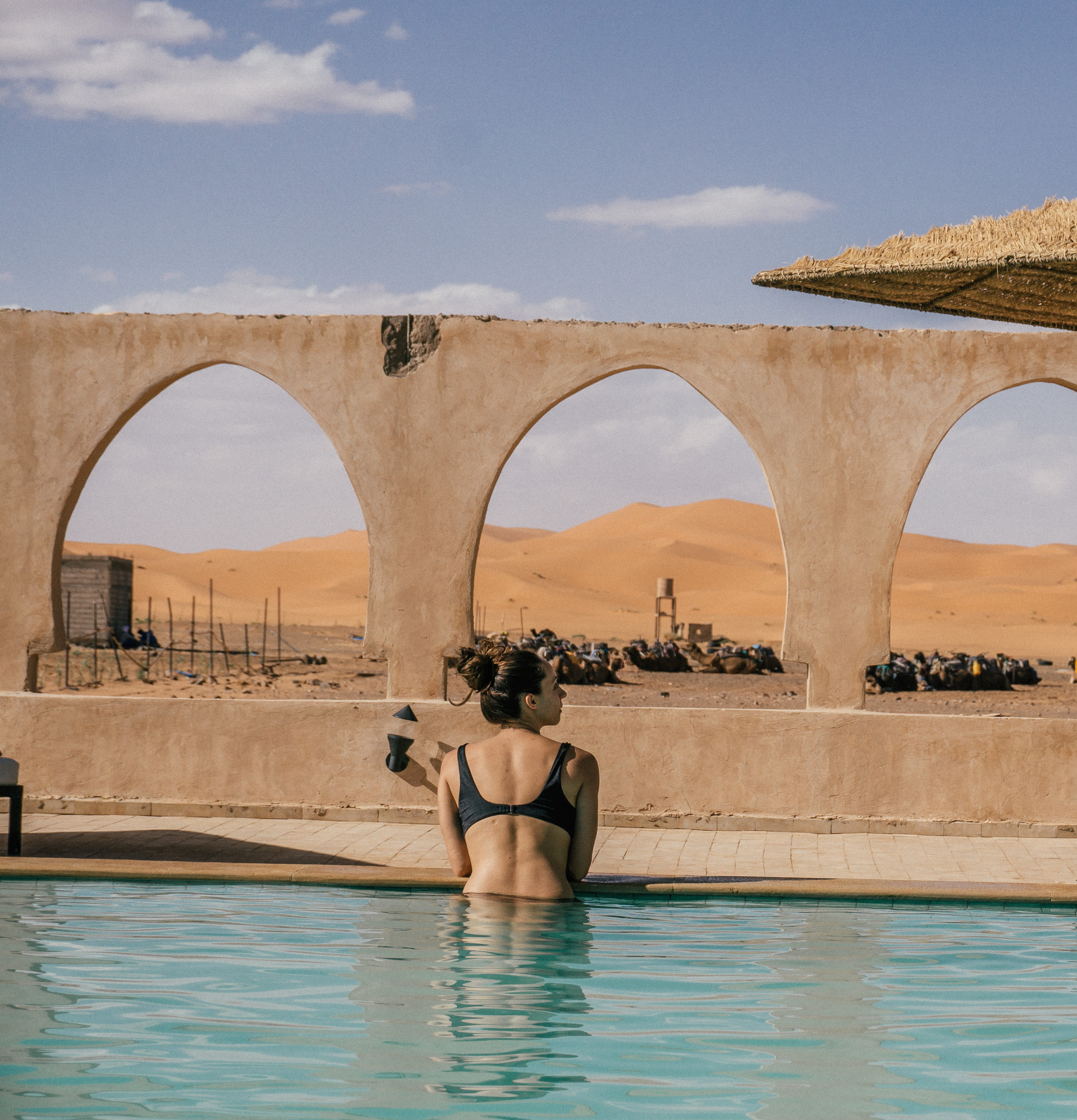 Swimming in Merzouga hotel with a view of the dunes and camels