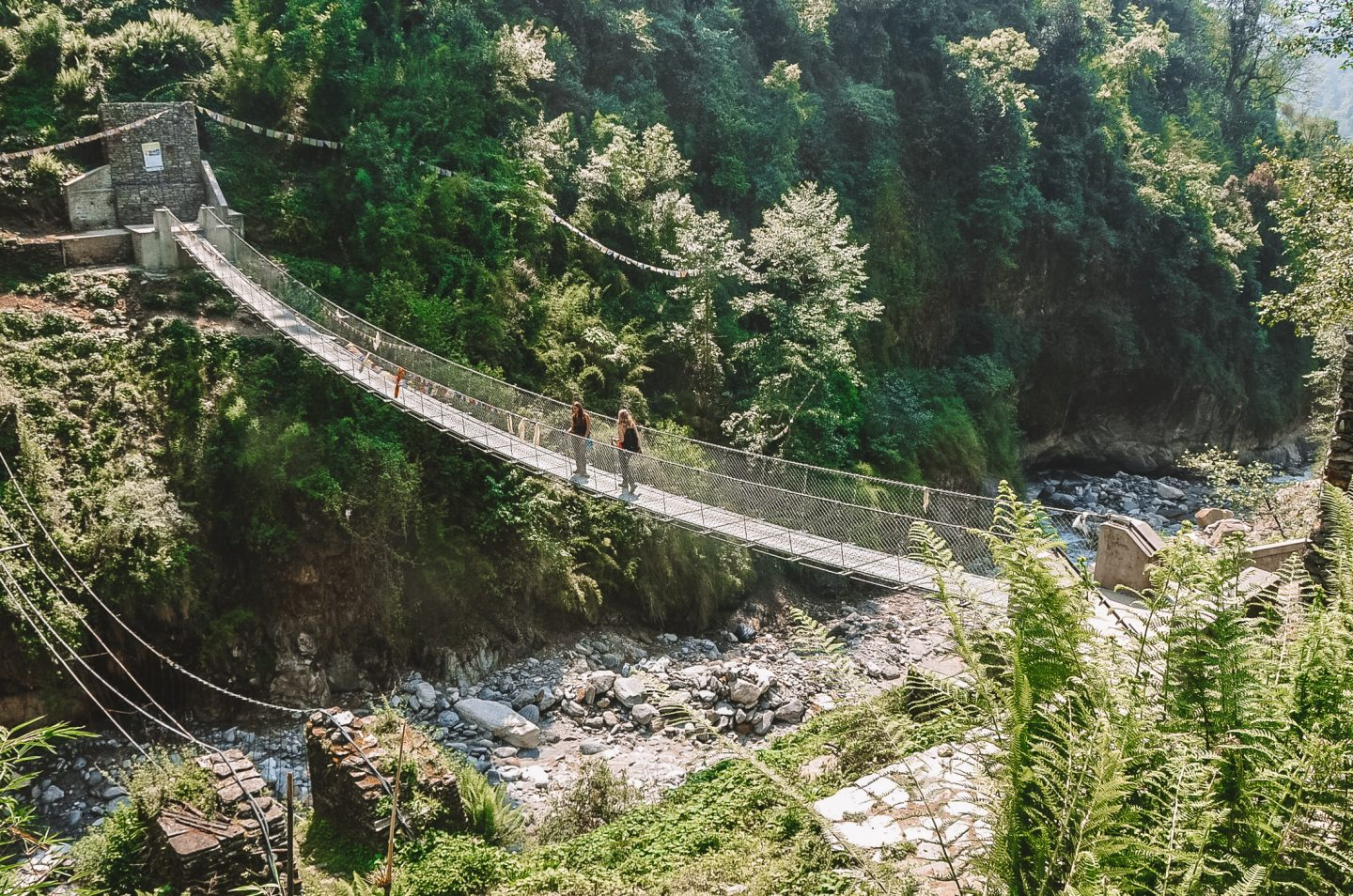 two girls crossing a bridge on the annapurna base camp trek nepal