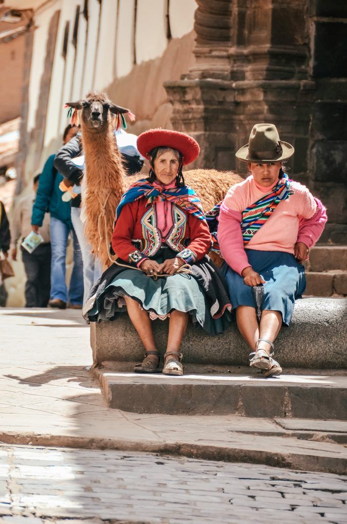 Why you need to visit Peru today - local women with alpaca