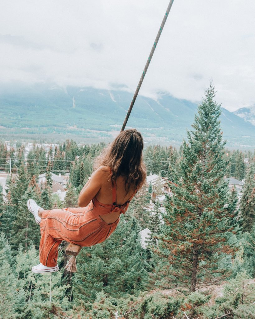girl in pink jumpsuit on canmore swing, banff