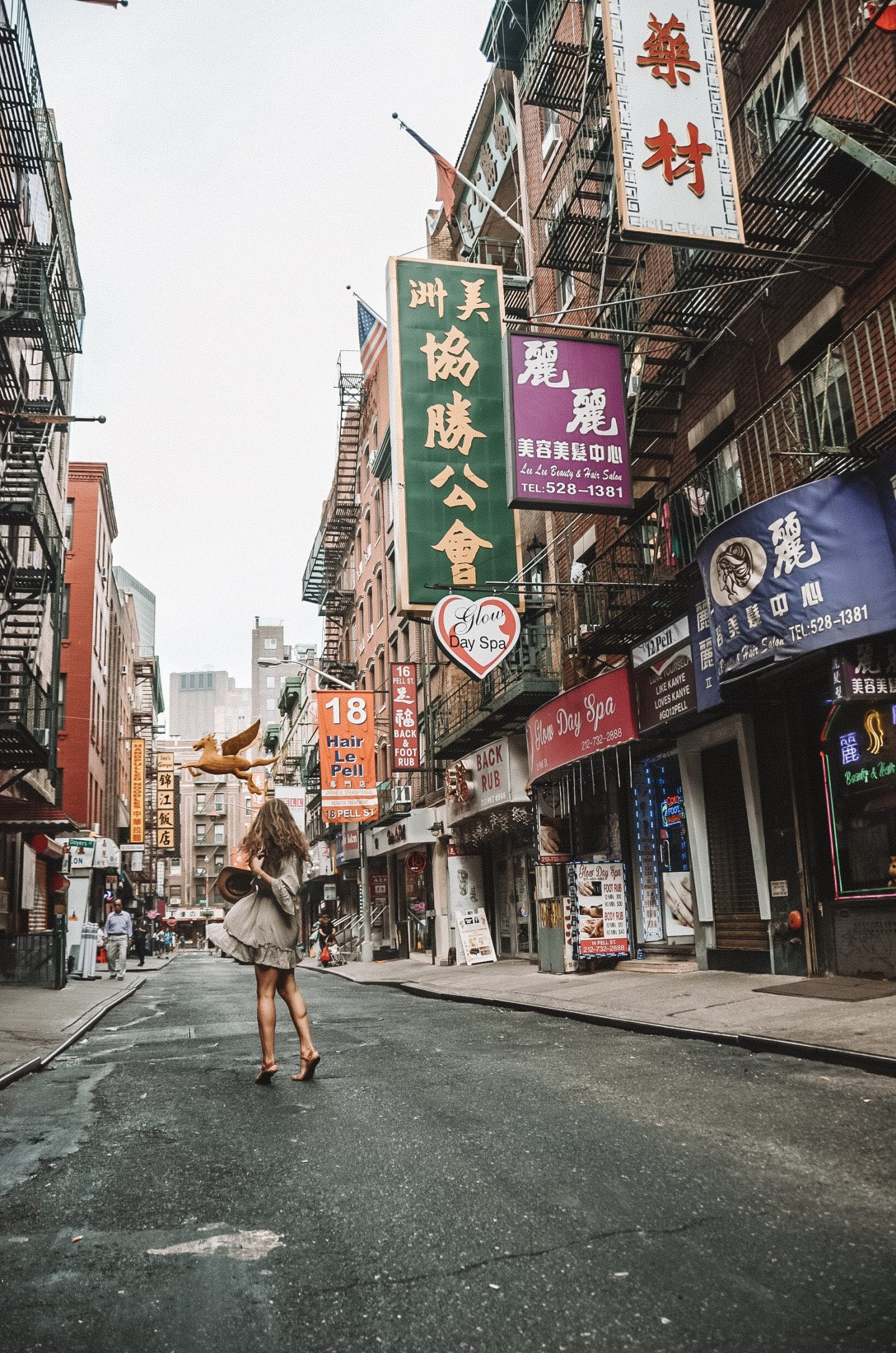 Girl twirling in green dress in Chinatown, NYC