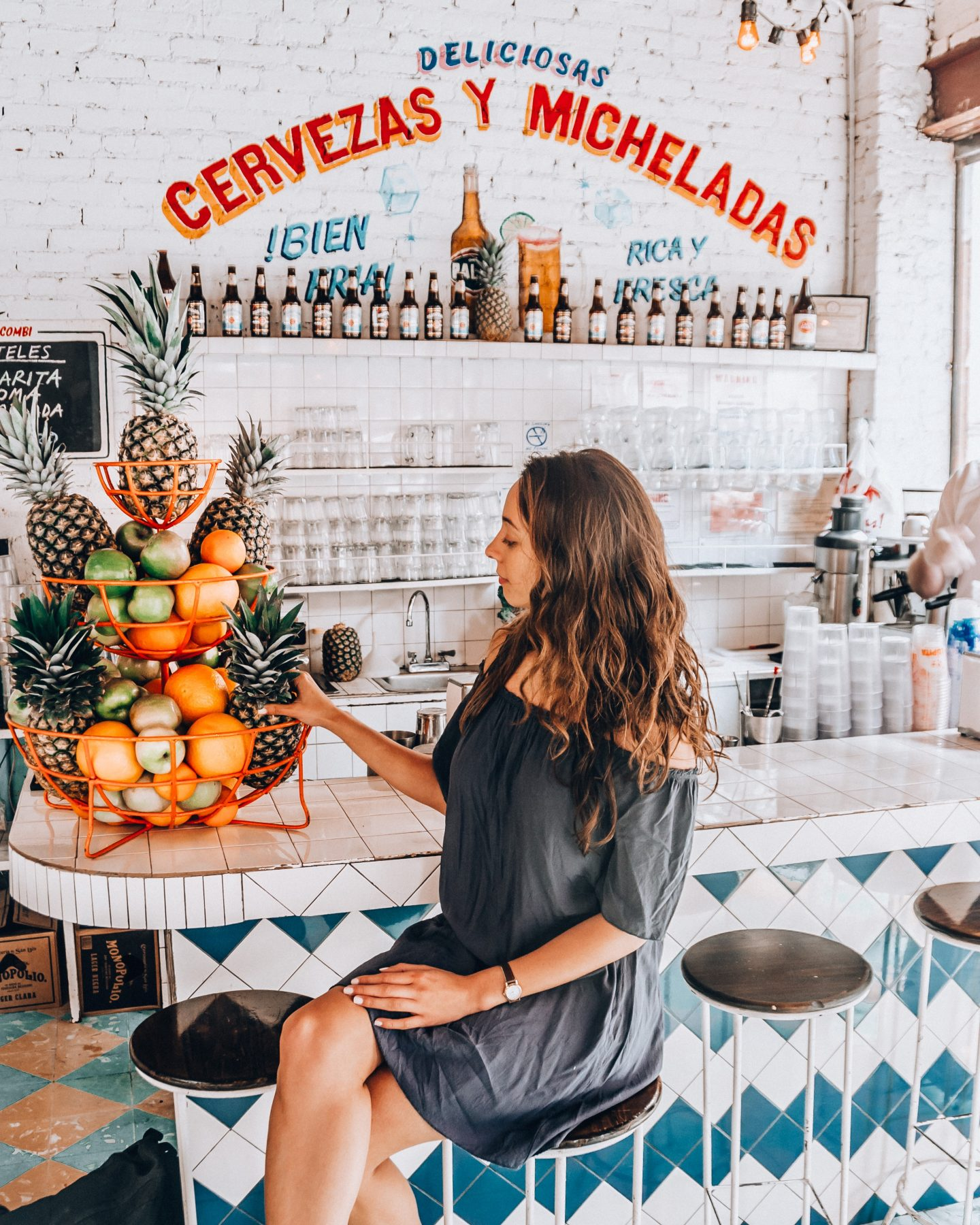 Girl in blue dress with bowl of fruit at taco restaurant in NYC