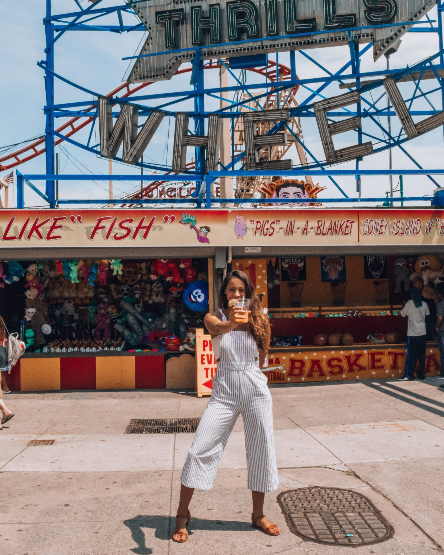 Girl in front of ferris wheel at Coney Island