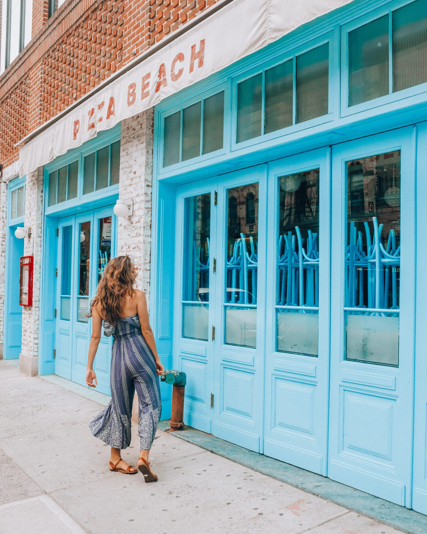 Girl in blue jumpsuit in front of blue wall of pizza restaurant in NYC
