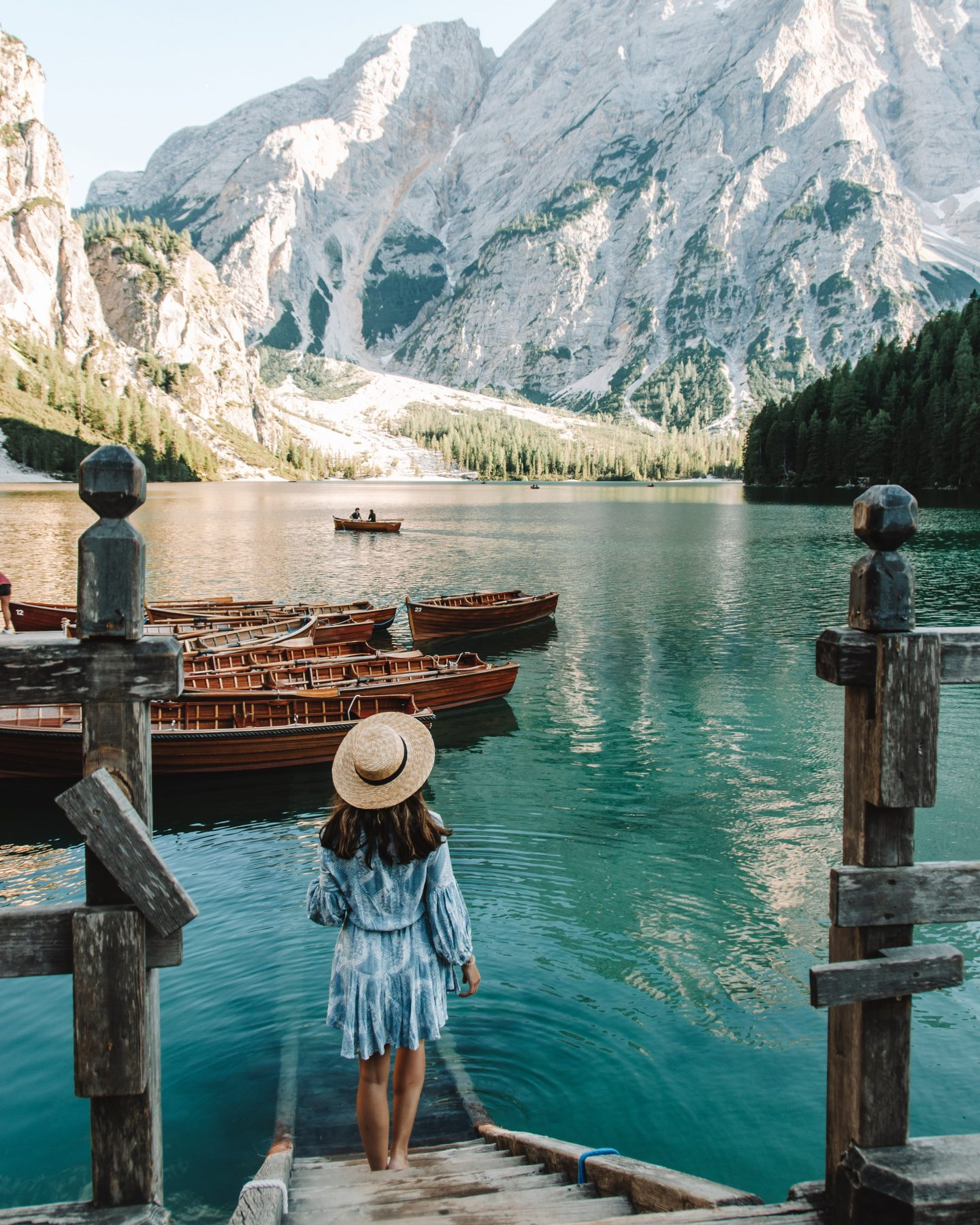 Girl in blue dress and a hat at Lago di Braise in the Dolomites, Italy