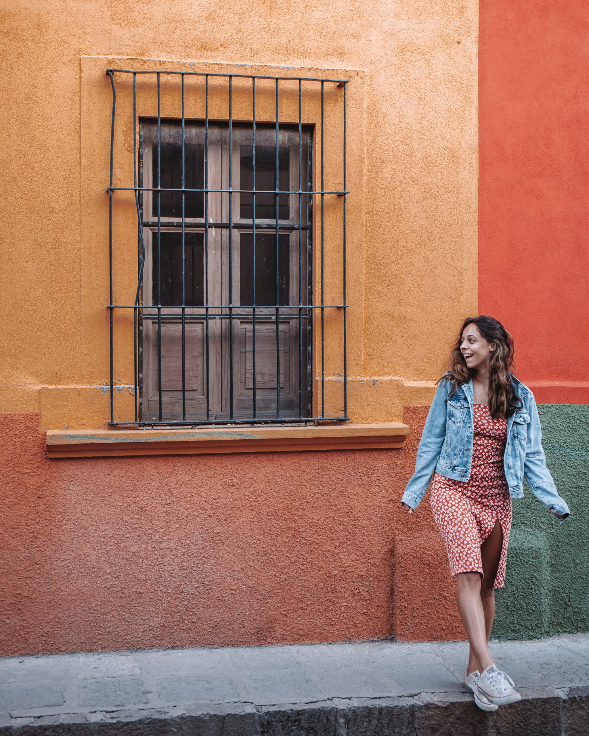 Girl in jean jacket in front of colorful wall