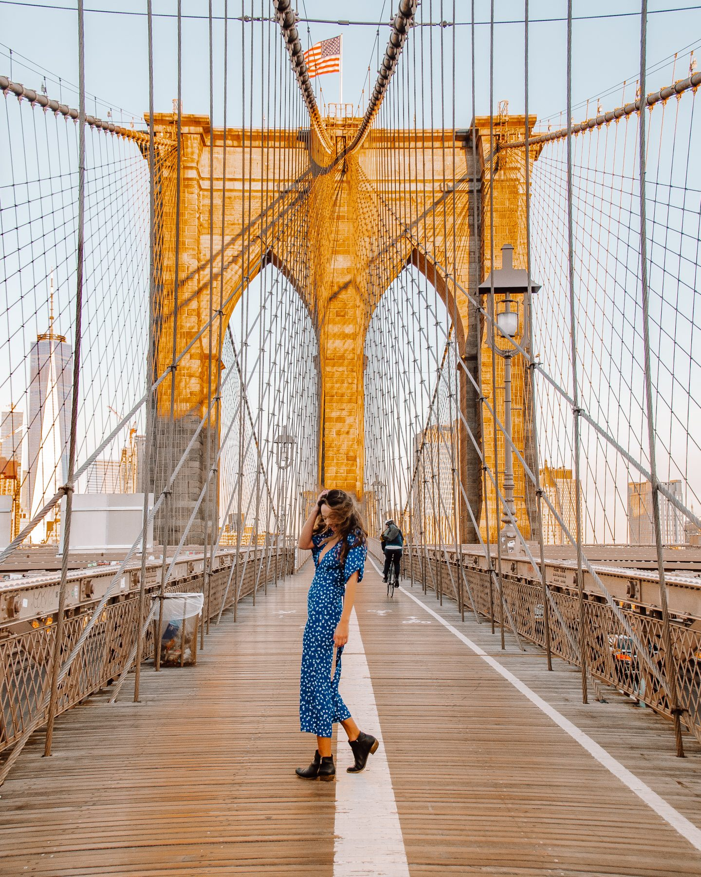 A girl in a blue jumpsuit on the Brooklyn Bridge at sunrise
