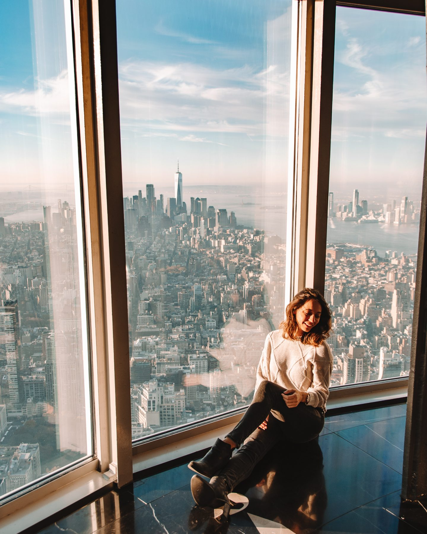 Girl sitting on 102nd floor of the Empire State Building in NYC