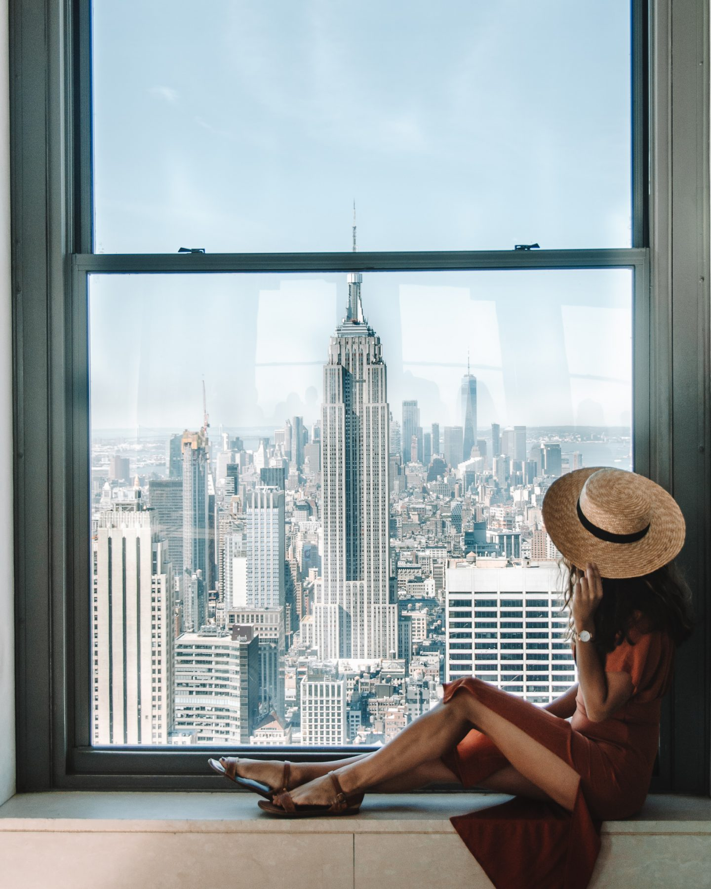 A girl in an orange dress sitting in a window at Top of the Rock