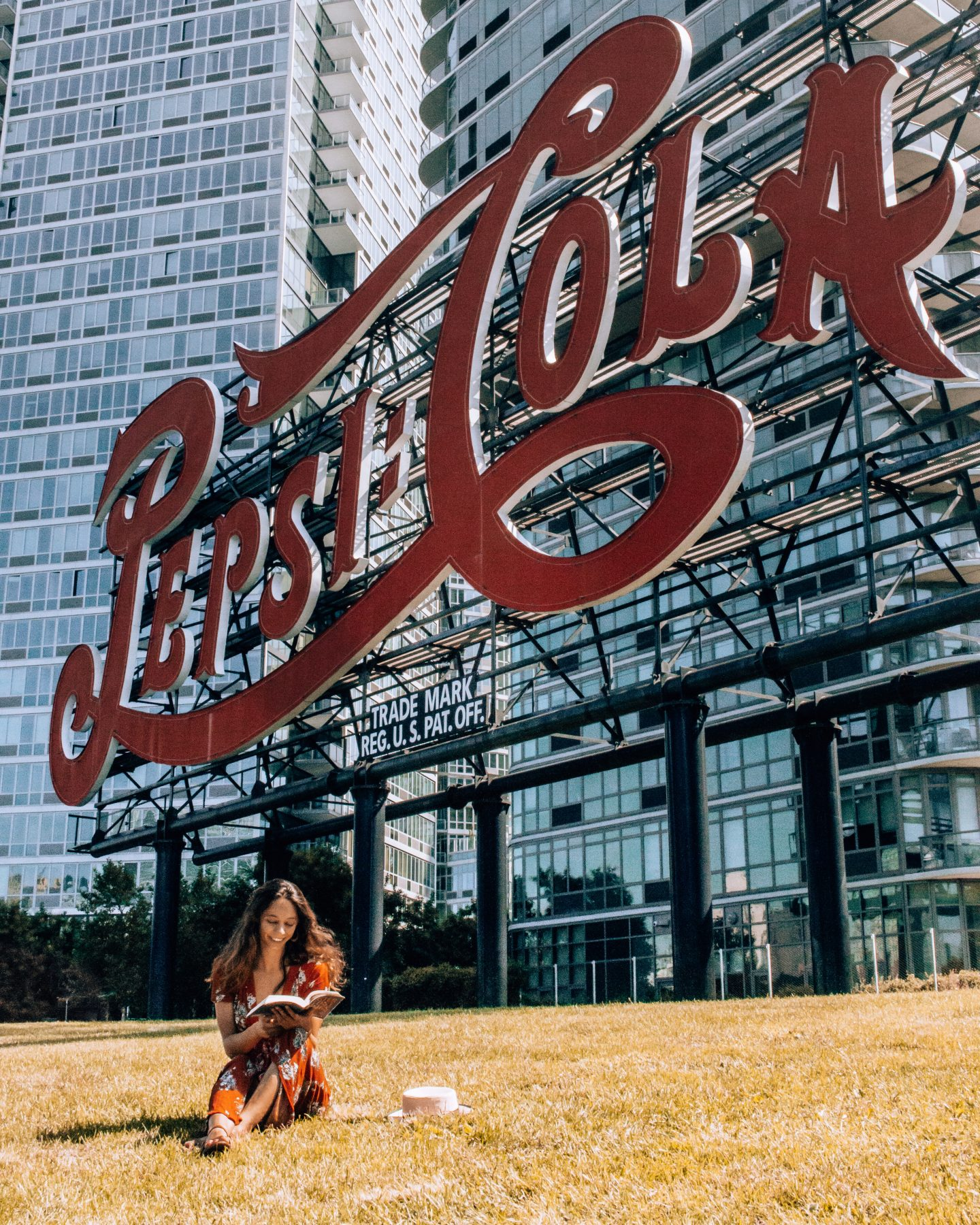 Girl reading a book at the Pepsi Cola Sign in Long Island City, NY