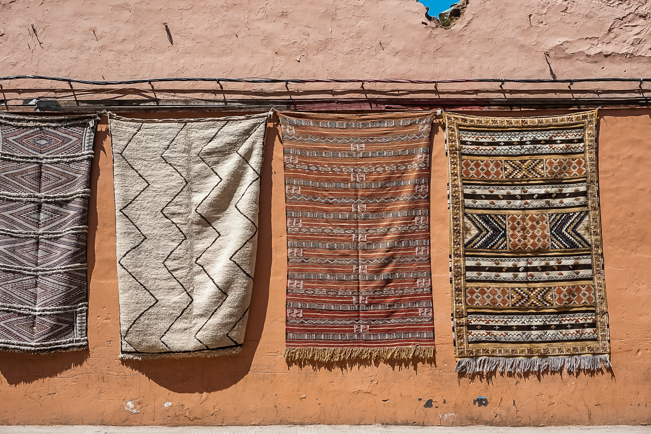 rugs hanging on a red wall in marrakech morroco itinerary