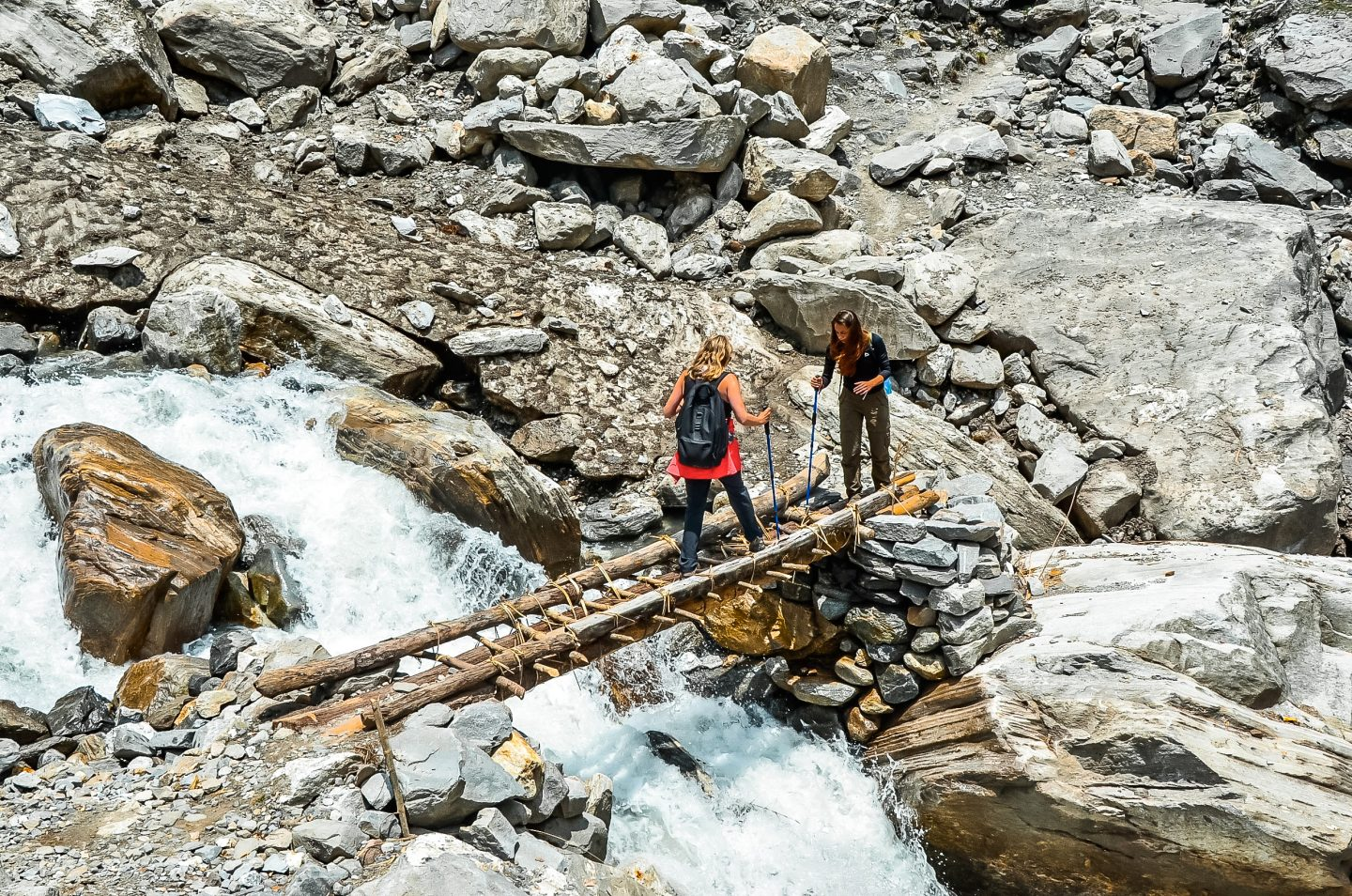 Mother and daughter cross over a river on the hike to annapurna base camp