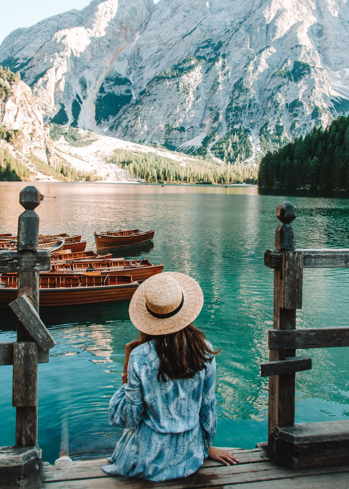 a girl in a blue dress sitting on the steps at lago di braies in the dolomites