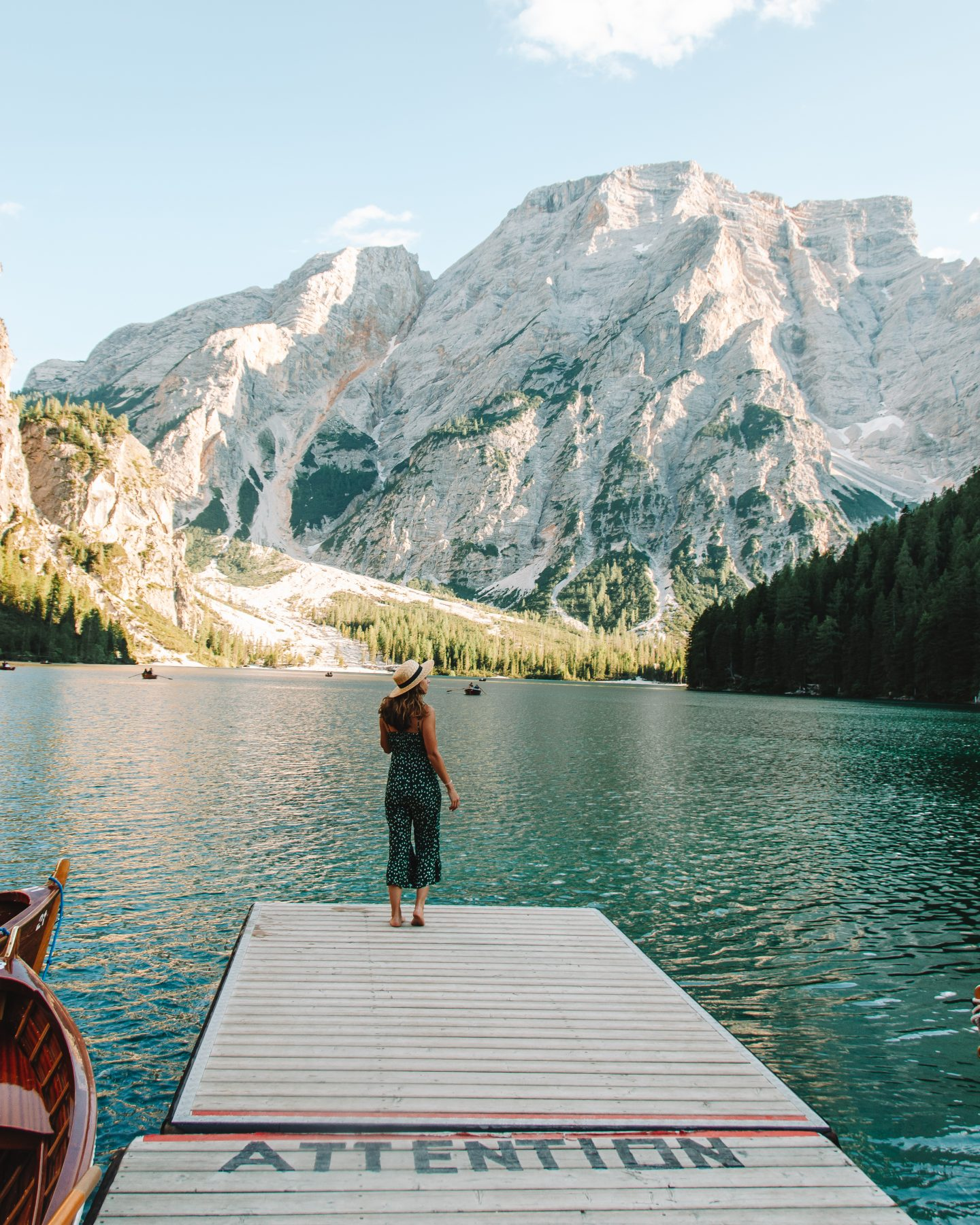 a girl on a dock in front of a lake in the dolomites, italy