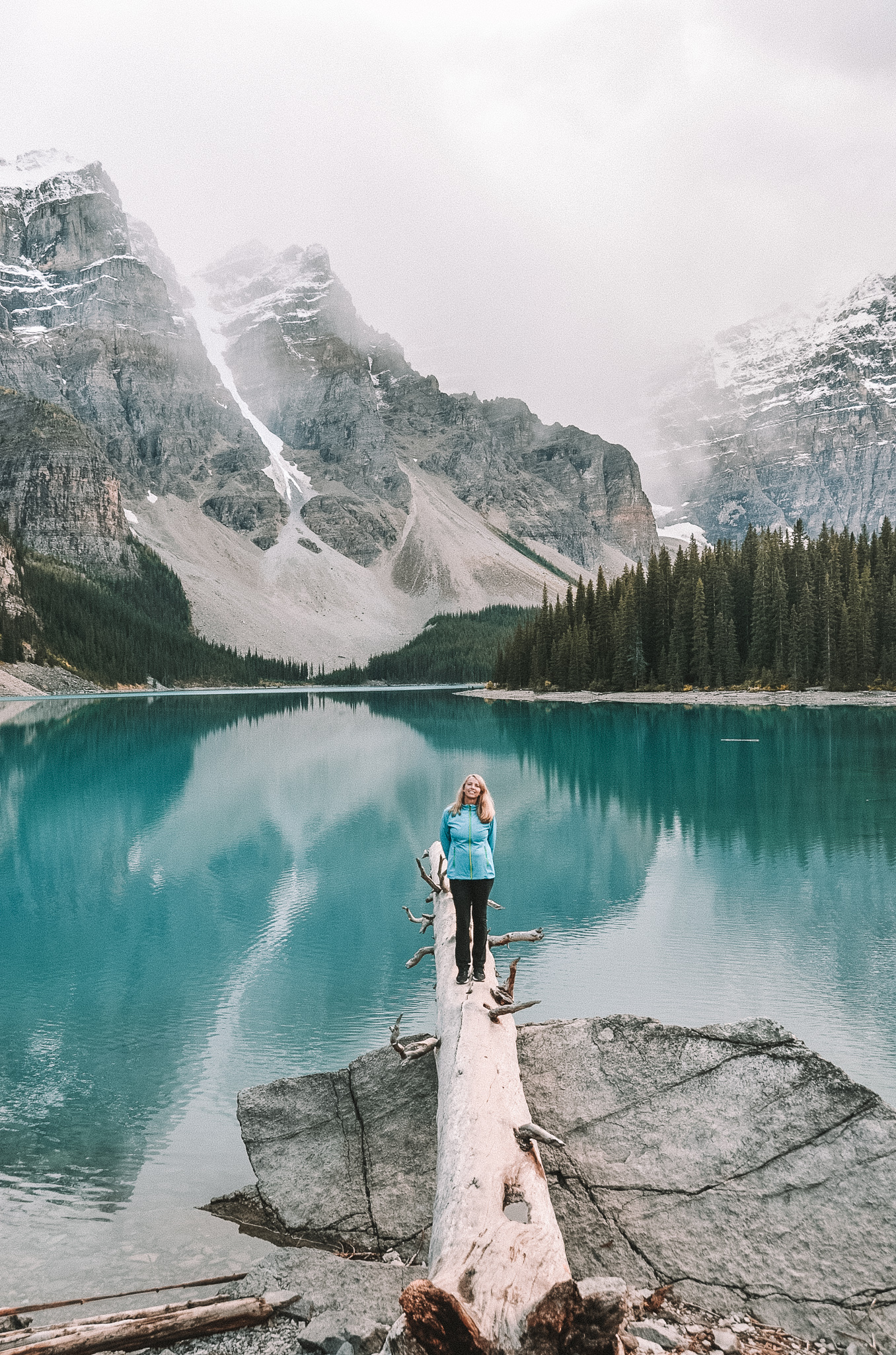 woman in blue jacket on log at moraine lake banff national park canada