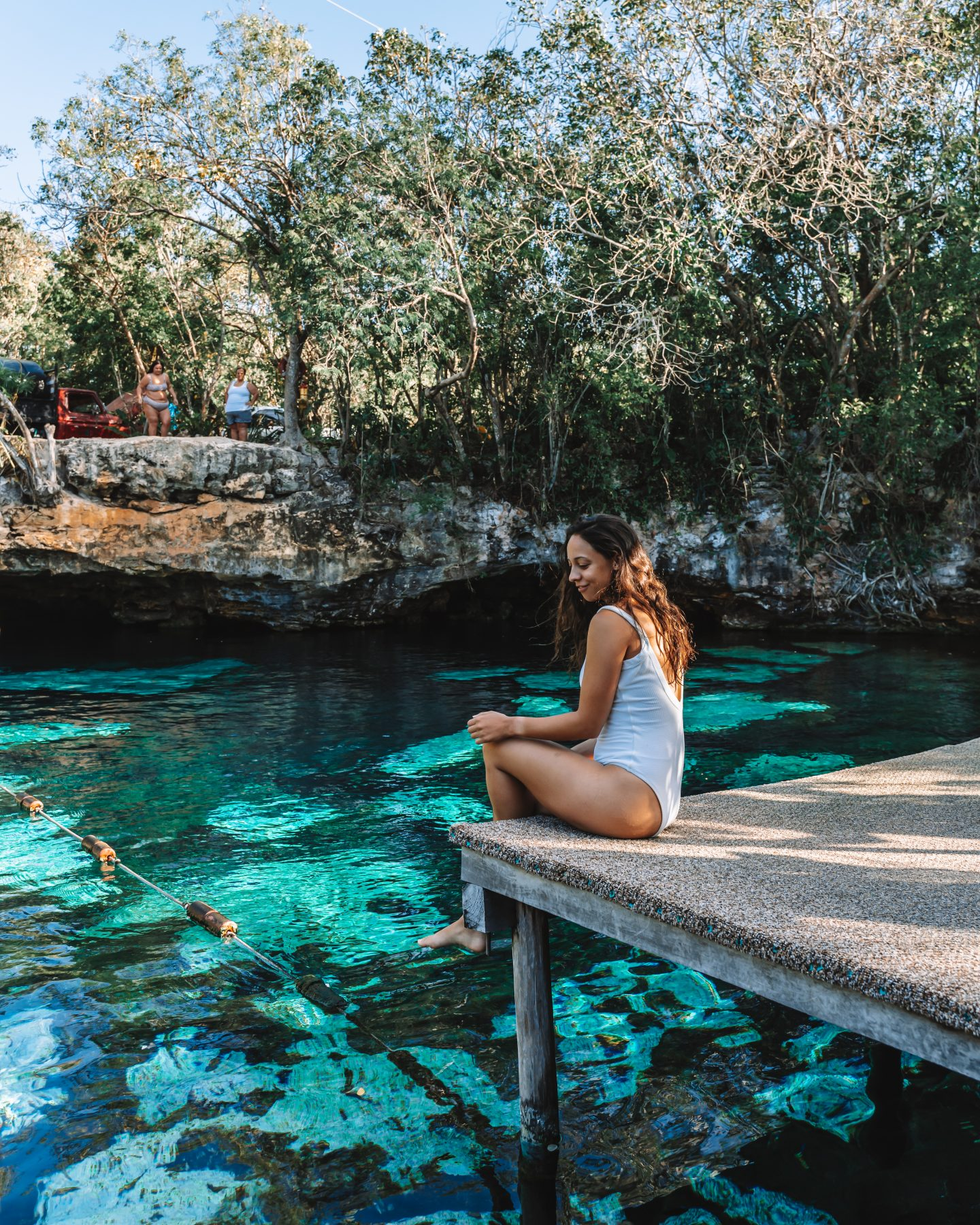 girl on platform overlooking clear cenote water