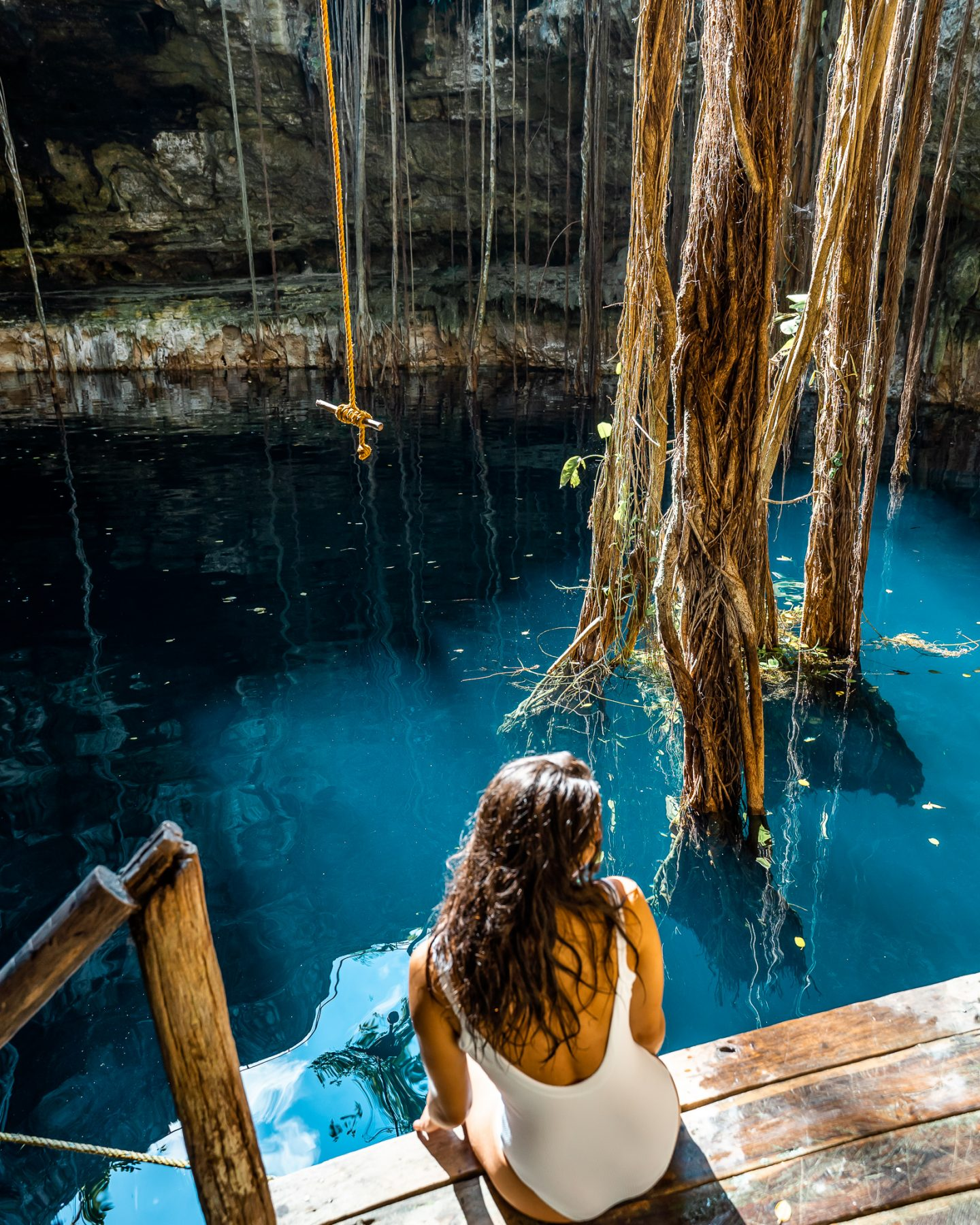 girl in white bathing suit at cenote oxman