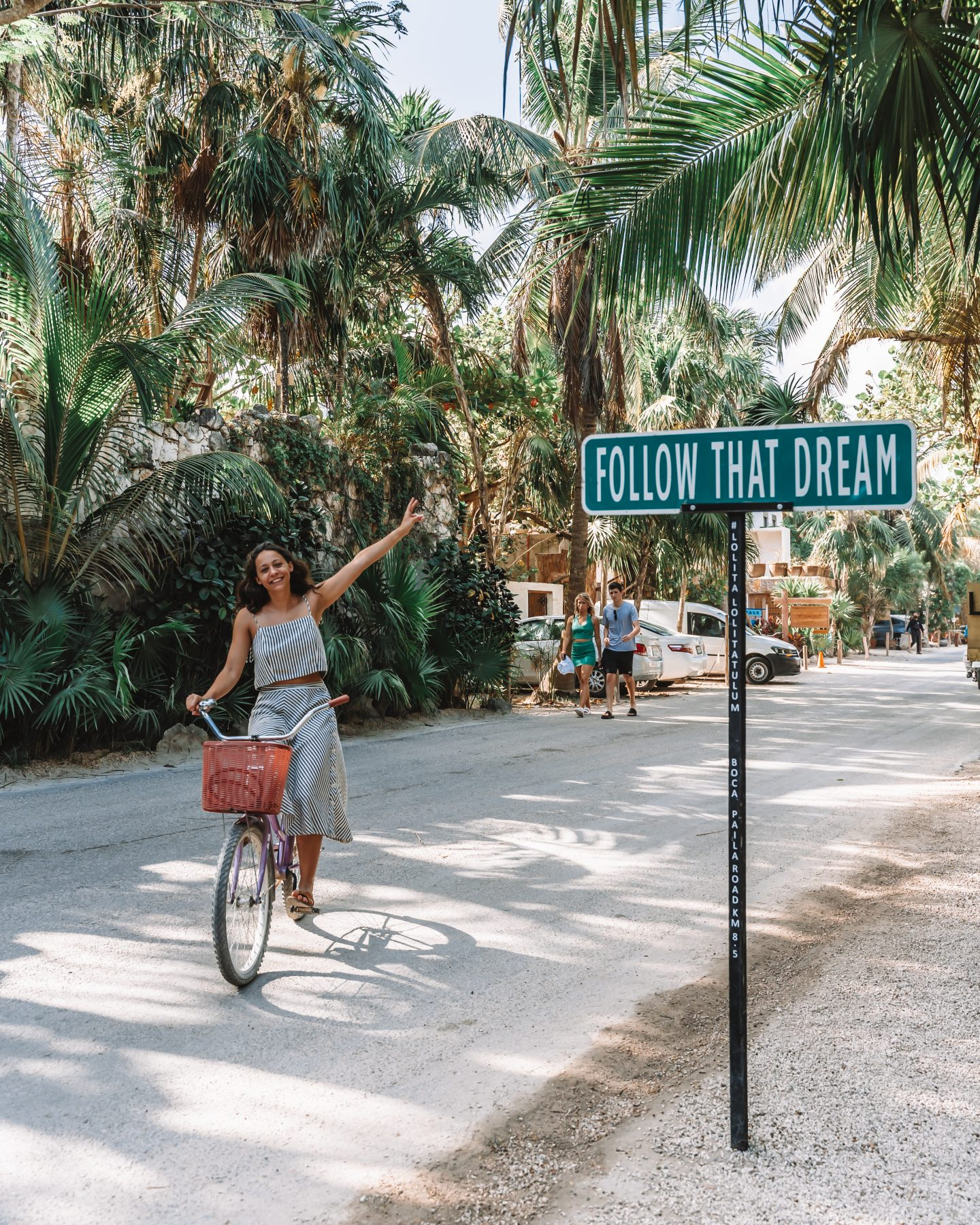 girl on a bike in front of the follow that dream sign