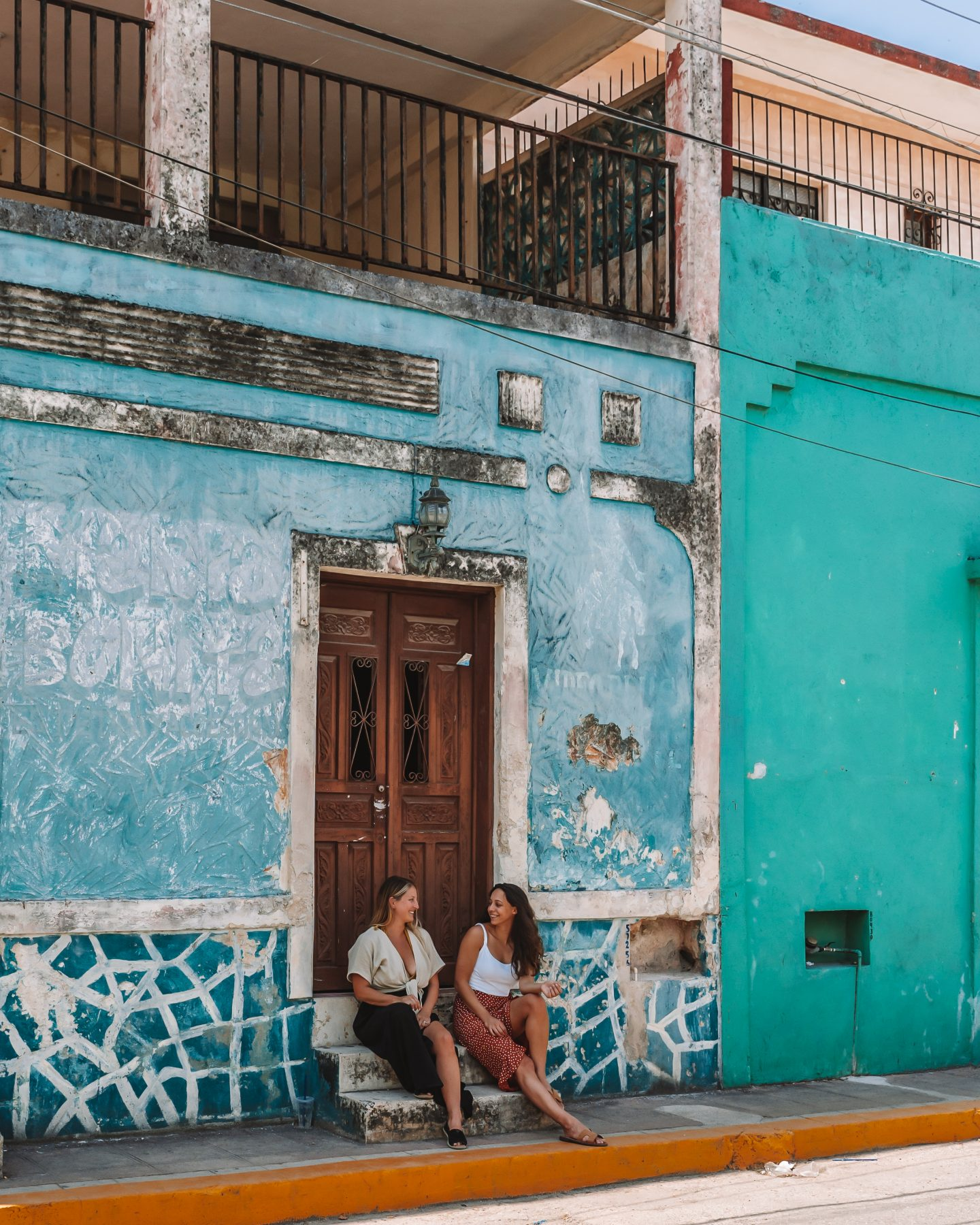 two girls in front of blue house in valladolid, mexico
